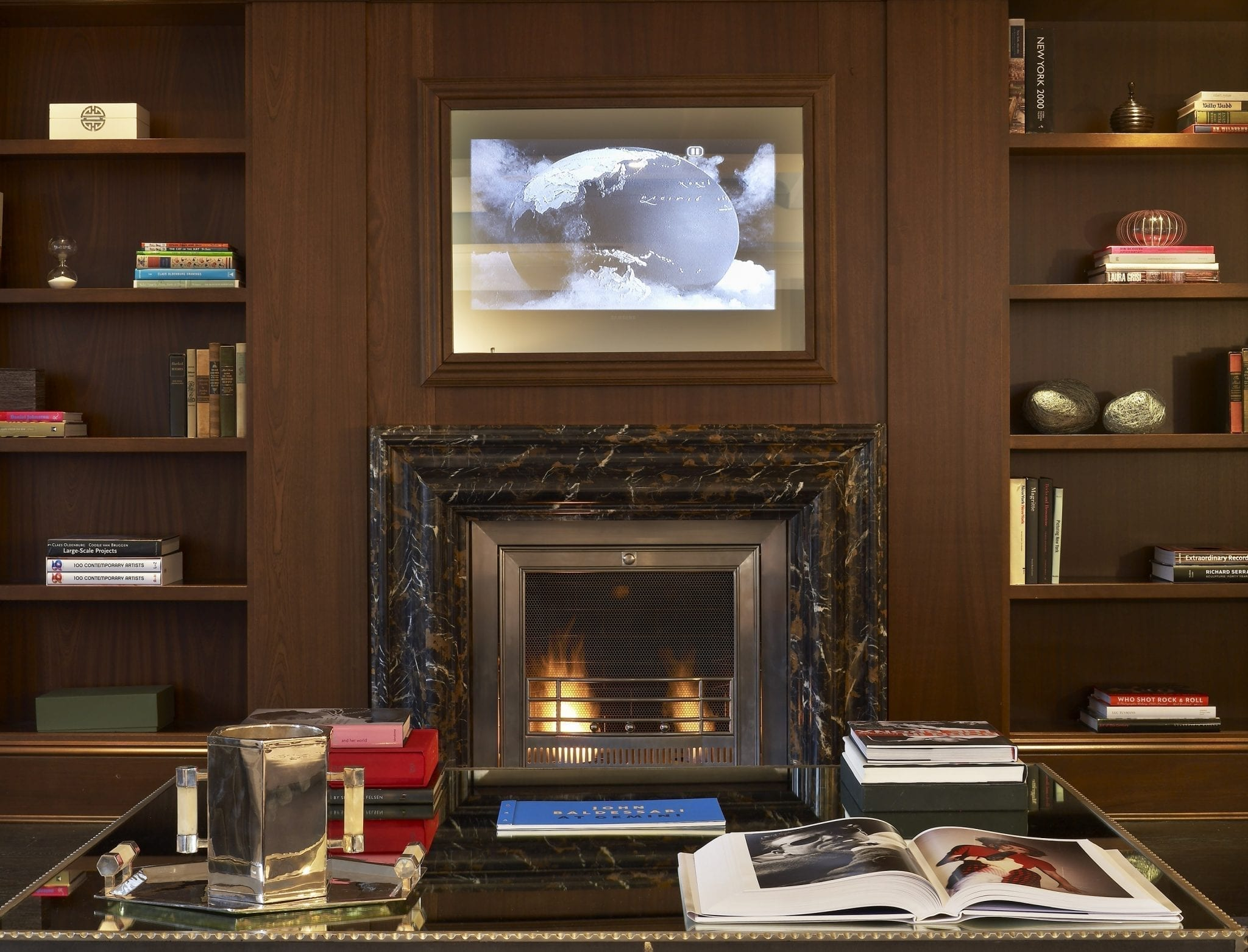 Close-up of the fireplace and flat screen television inside the sitting area of The Surrey Hotel's Presidential Suite. At the sides are book cases set into the wall paneling, with a lit fireplace.