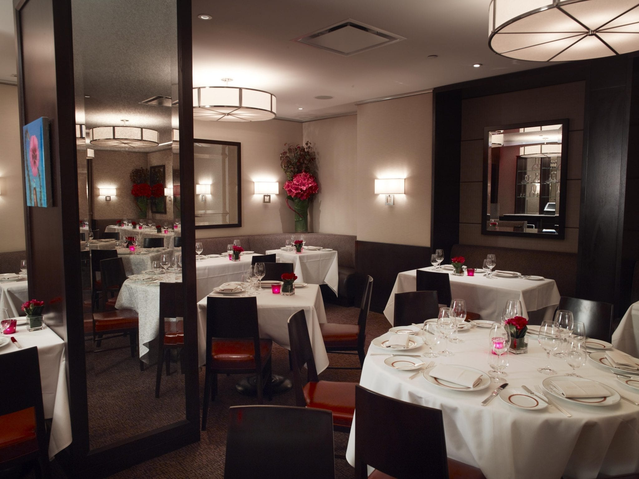 Corner of a dining area, inside Cafe Boulud. A mix of round and square tables are placed around the room, each dressed in a white cloth. A very long table is placed against the far wall, with booth seating on one side. Photography by B. Milne.
