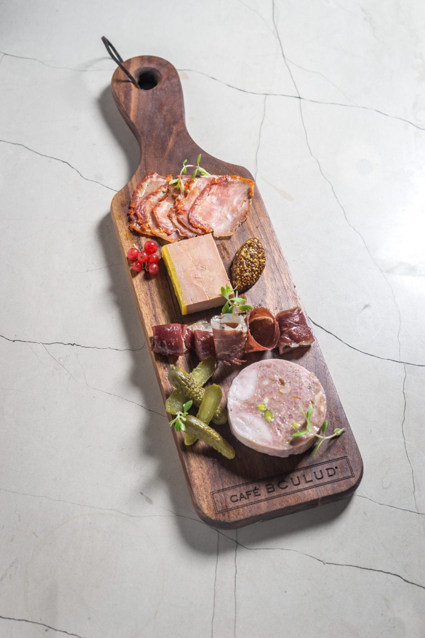 Close-up of a Charcuterie bread board, served inside Cafe Boulud. Photography by Paul Wagtouicz.
