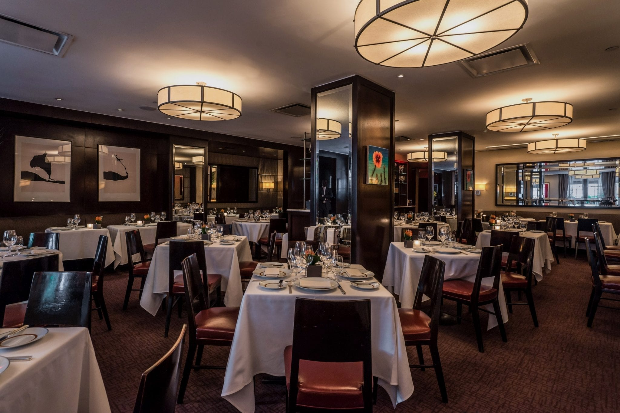 Long view of the Cafe Boulud dining room Square tables are placed around the room, each dressed in a white cloth. This room is warmly lit from round paneled lamps light the room. Photography by Paul Wagtouicz.