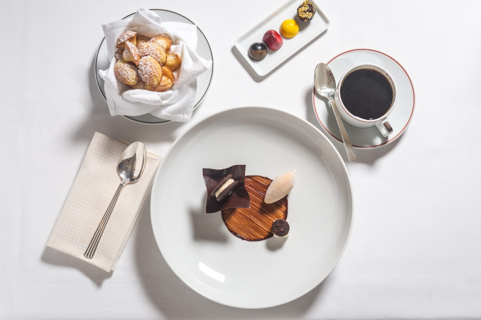 Assorted deserts pastries, served from Cafe Boulud. A saucer holding a spoon and coffee is placed just beside. Photograph by Paul Wagtouicz.