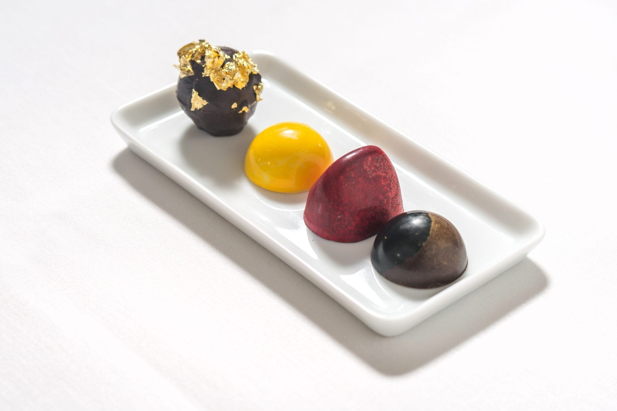 Long white tray, holding a set of truffles at Cafe Boulud. Photograph by Paul Wagtouicz.