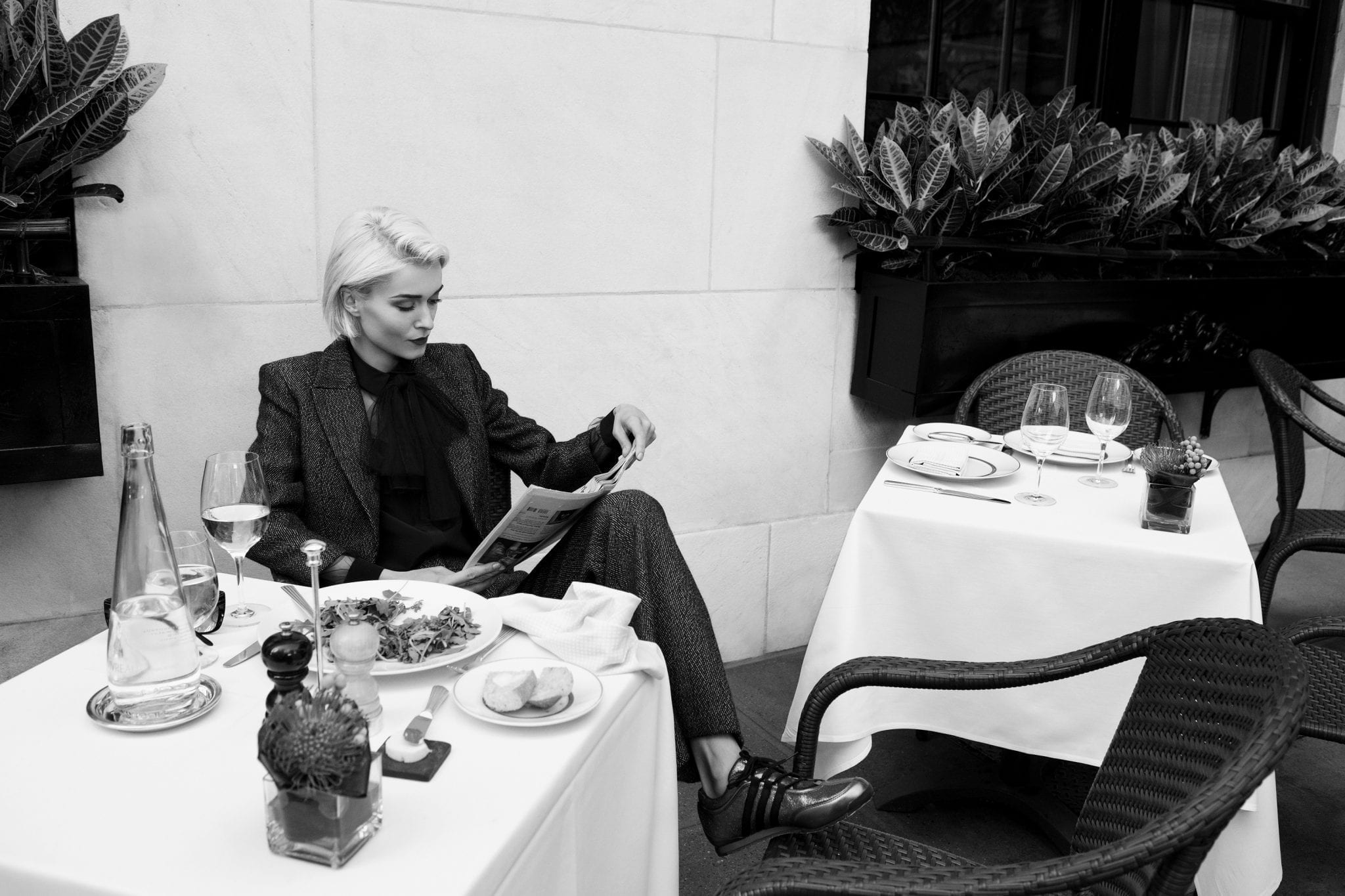 Classy patron enjoying a meal on Cafe Boulud's patio. Her head is cast down, reading her magazine. A meal, along with a side plate of dinner rolls has been placed at her table. A glass is filled with white wine. Amy Hanna Marketing, 2014