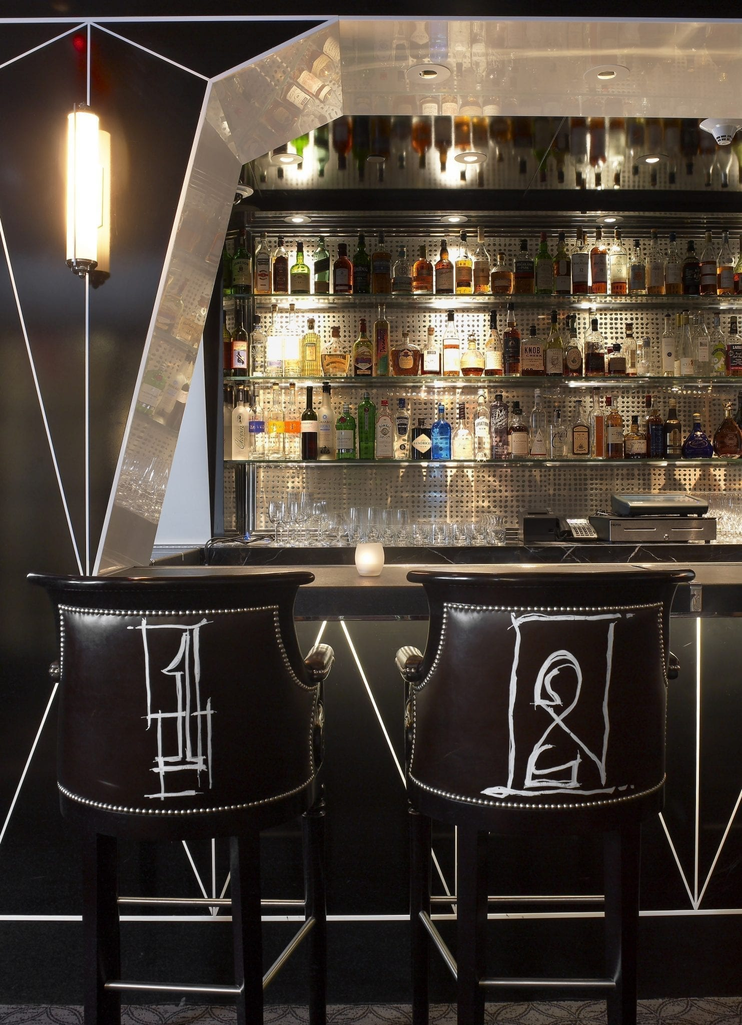Two stylish bar stools in Bar Pleiades, with design by Jimmie Martin. White scrawls make up the deep brown upholstered back of each stool. In front, long clear shelving holds the bar's favorite drinks for mixing.