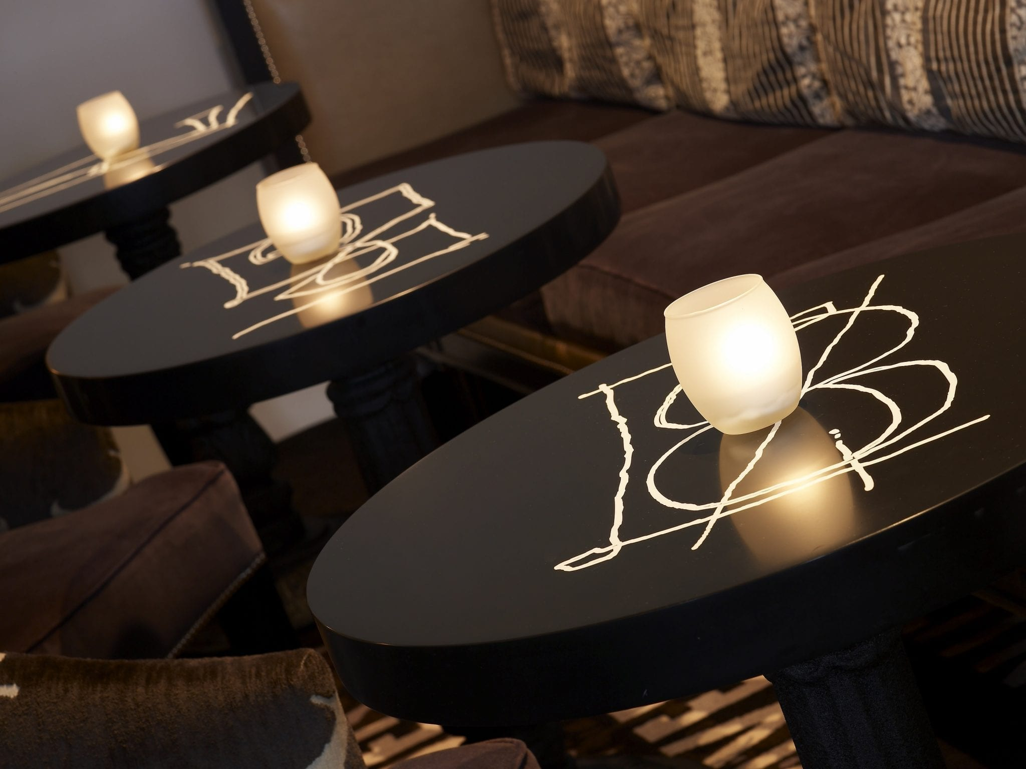 Close up of Bar Pleiades' seating area, featuring stylish tables designed by Jimmie Martin. In his style, white letters are scrawled large, at the center. A votive glass holds a lit candle, placed on each table.