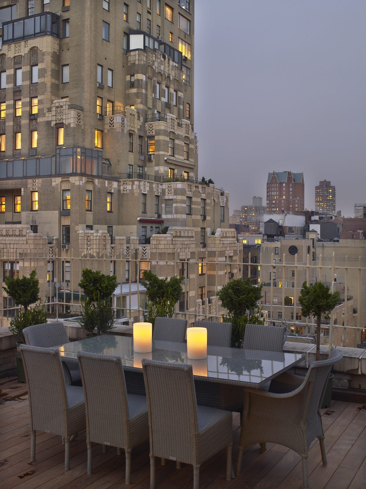 Wide dining table set upon The Surrey's Penthouse Suite terrace. Two cylindrical candles are placed on the middle of the table, with 8 chairs placed. The Skyboxes of Carlyle Hotel can be seen from this area.