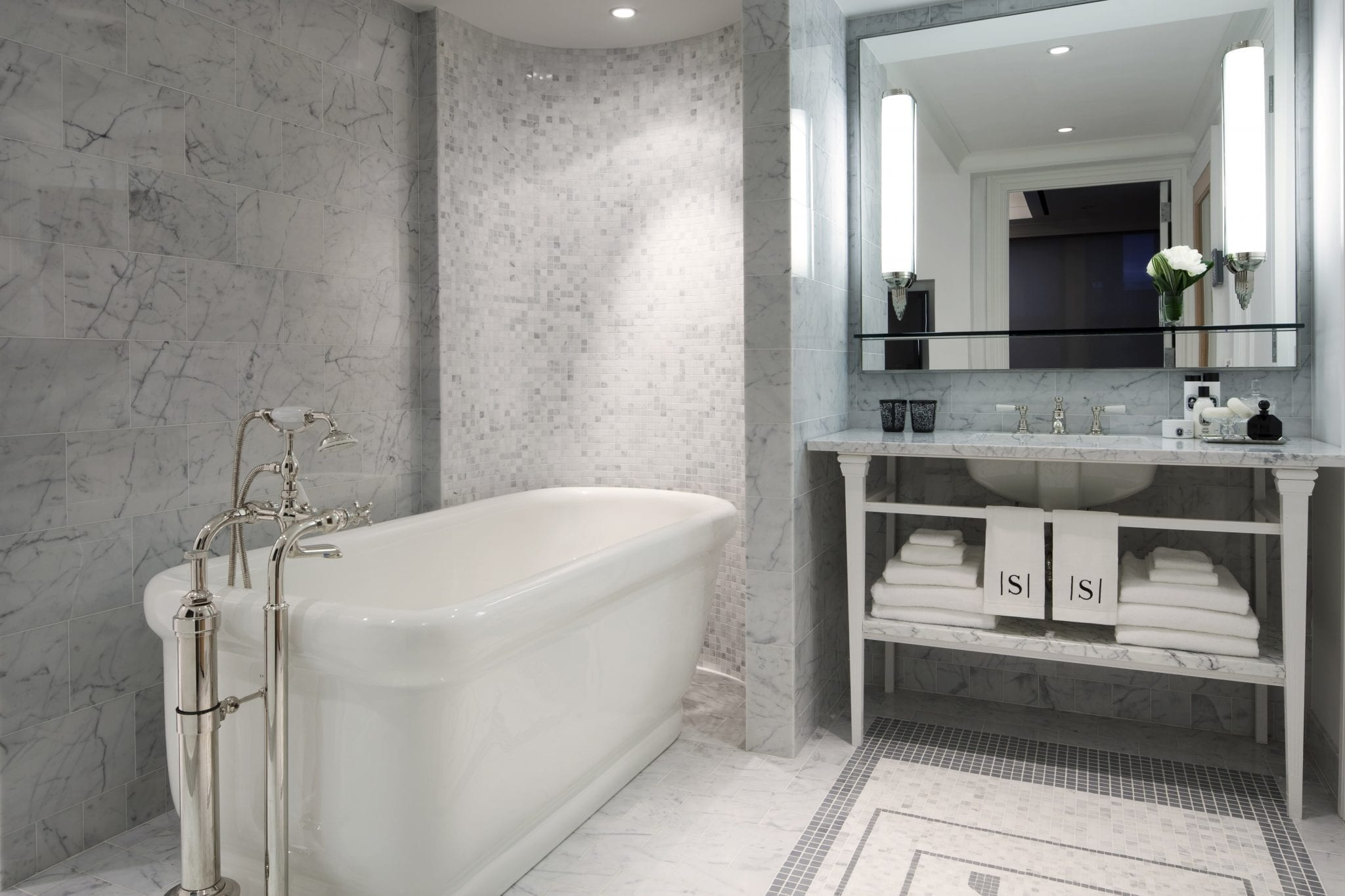 The Presidential Suite's Bathroom, inside The Surrey Hotel A large white basin bathtub is placed aside from the marble sink. A large mirror hangs on back wall, with complimentary toiletries. Towels are neatly stacked on the shelves below. Photo by Tom McWilliam.
