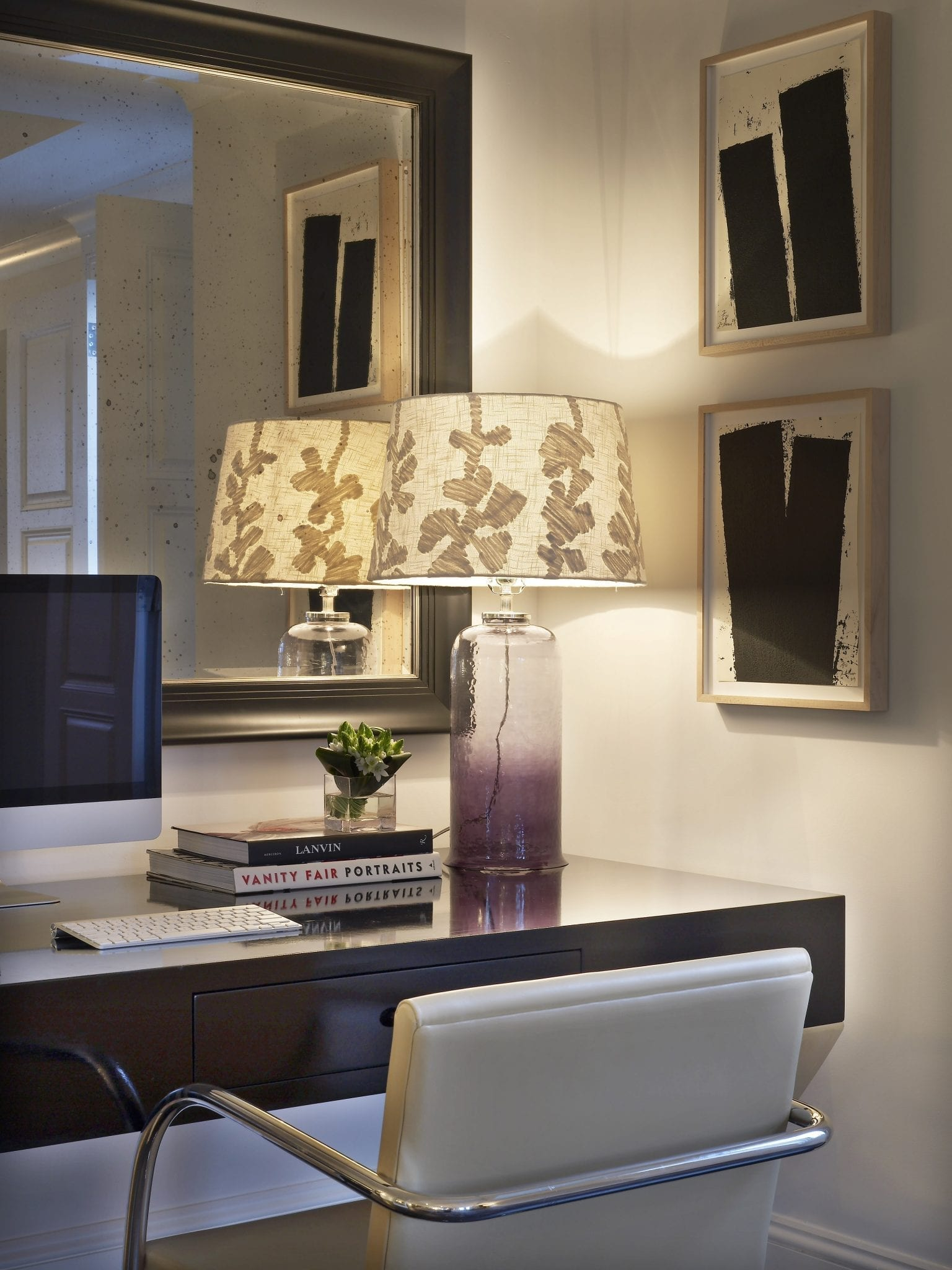 Close up of a corner desk area, inside the Surrey Hotel's Presidential Suite. The lamp is turned on, placed just beside two books and a small plant vase stacked up.