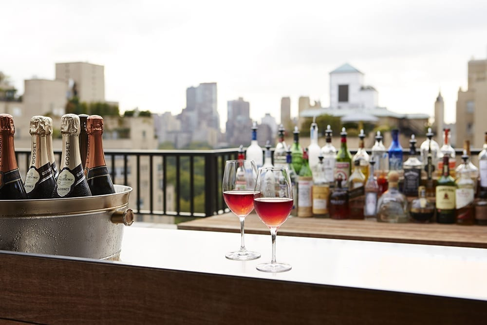 Wooden bar kiosk on the far end of The Surrey Hotel's rooftop garden. Two wine glasses are set down, ready to be served. Behind, is a wooden table holding a mix of alcoholic beverages and mixers.