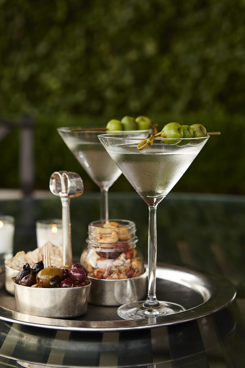 Close up of a round serving tray holding two martinis. Some jars of dried fruit and nuts are placed alongside.