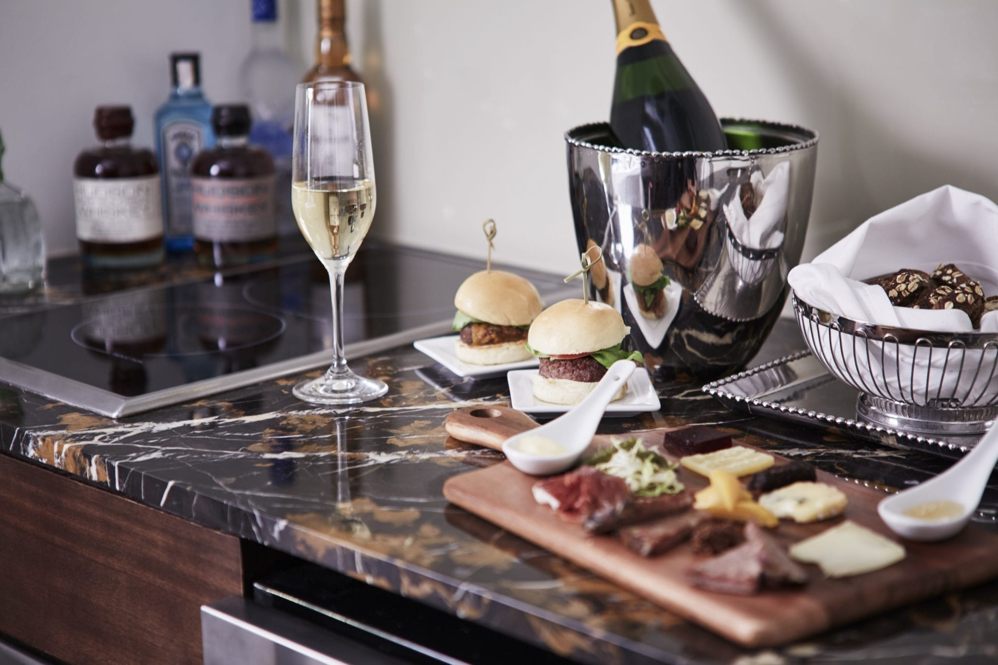 Close up of the marbled kitchen counter top inside The Surrey Hotel's Studio Suite. A cutting board holds cheeses and meat, with two burgers prepared on small square trays. A bread basket is uncovered, placed just to the right of the wine's ice bucket. A single wine flute has been filled, with twin burners on the surface behind.