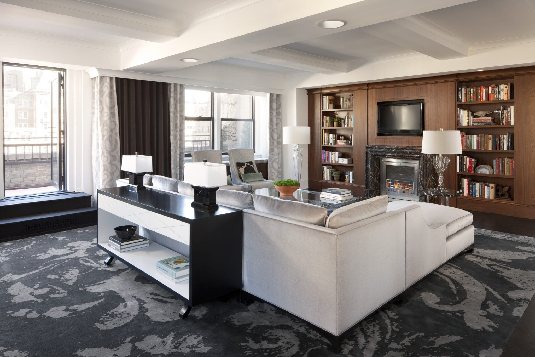 Perspective view of the living room area of The Surrey Hotel's Presidential Suite. Behind the L-shaped couch is a door leading out to the terrace. Across from the seating area is a wall panel with bookcases and HD TV inset. A lit fireplace is below the TV.