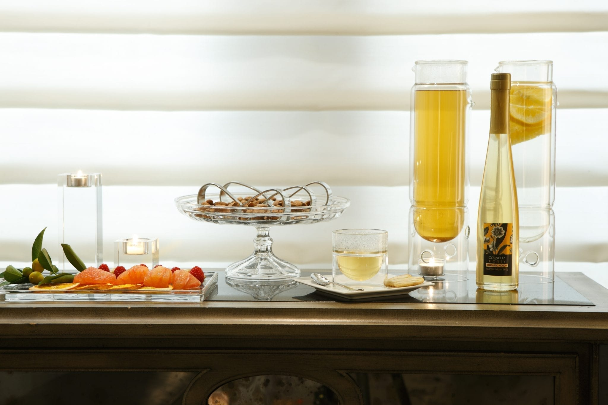A wine and snack spread placed in the parlor inside The Surrey's Cornelia Spa. A platter of cookies is placed center, with a white square platter holding a bit of honey wine and a cookie.
