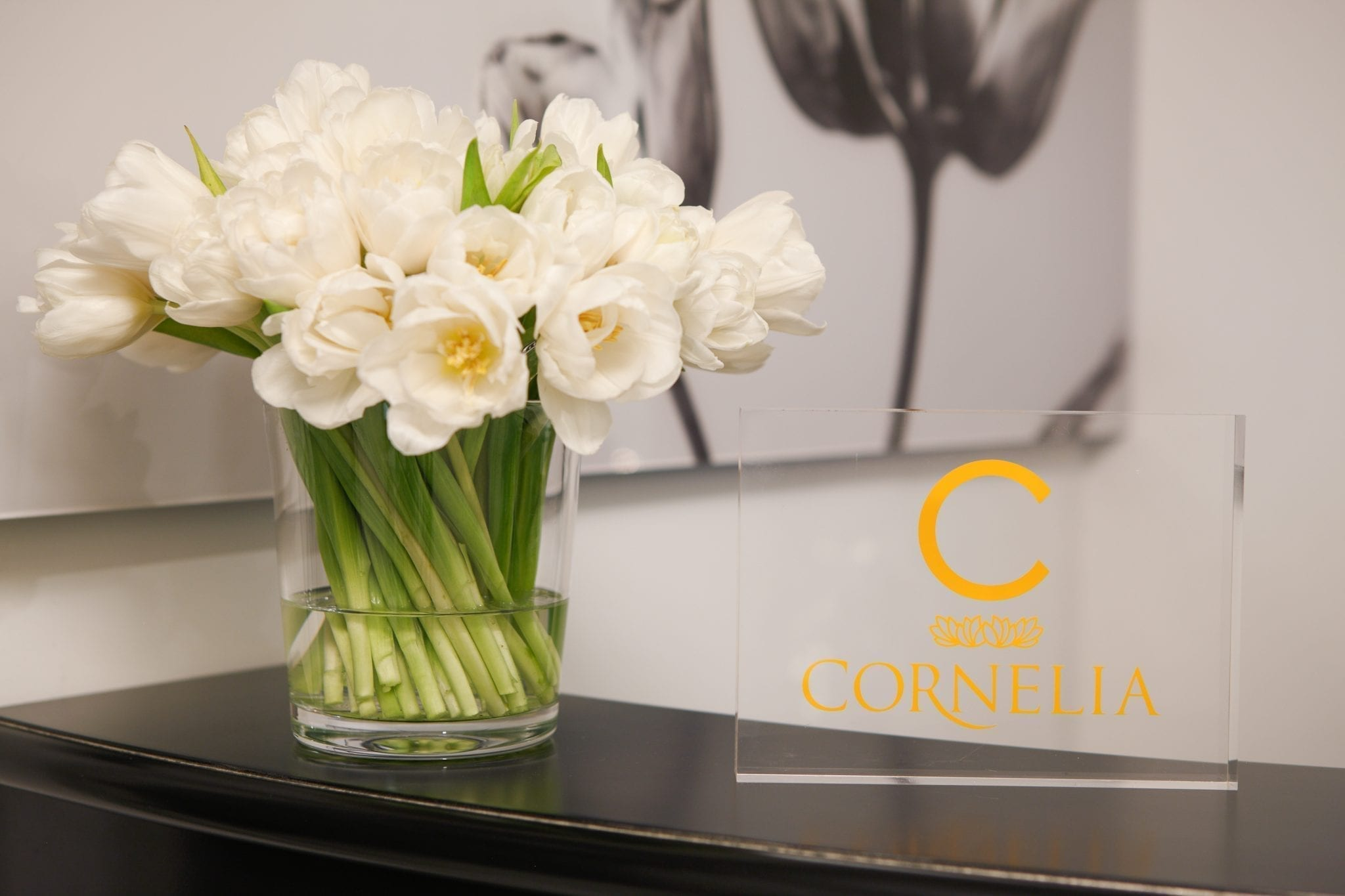 Close-up of the front reception desk of the Cornelia Spa. Next to the clear logo placard is a clear glass holding white roses.