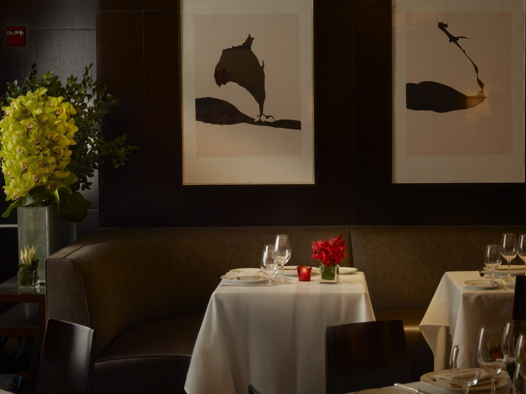 Close-up of a romantic table setting inside Cafe Boulud. The booth seats scoop behind the square table, the booth seat going all along the wall. The table has two empty goblets, placed beside a small flower pot and votive candle. Large paintings hang above, on the back wall.