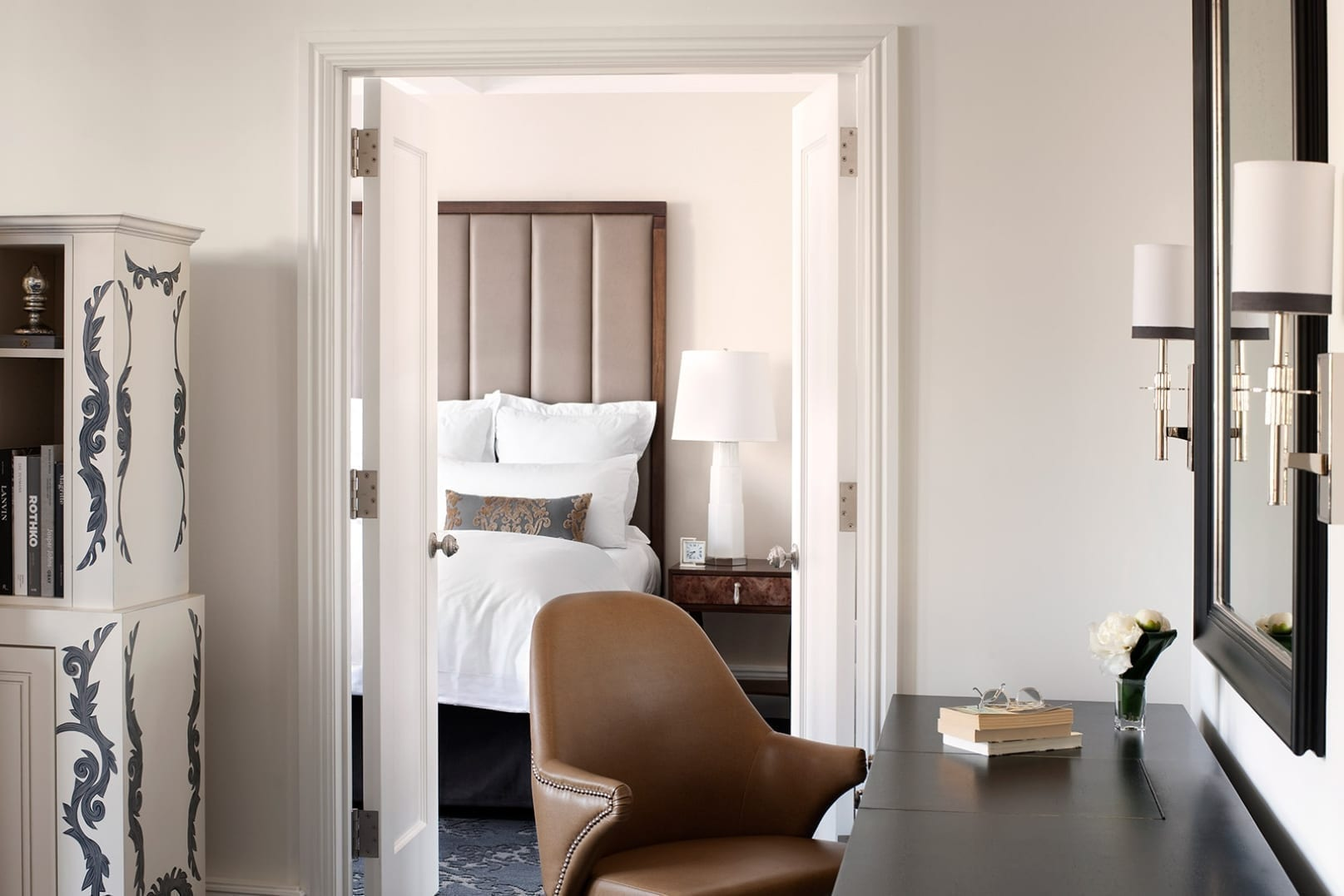 View from the living room of a Ultra Suite, inside The Surrey. A brown chair is seated at the wide black desk area on the right. Open double doors lead to the bedroom.