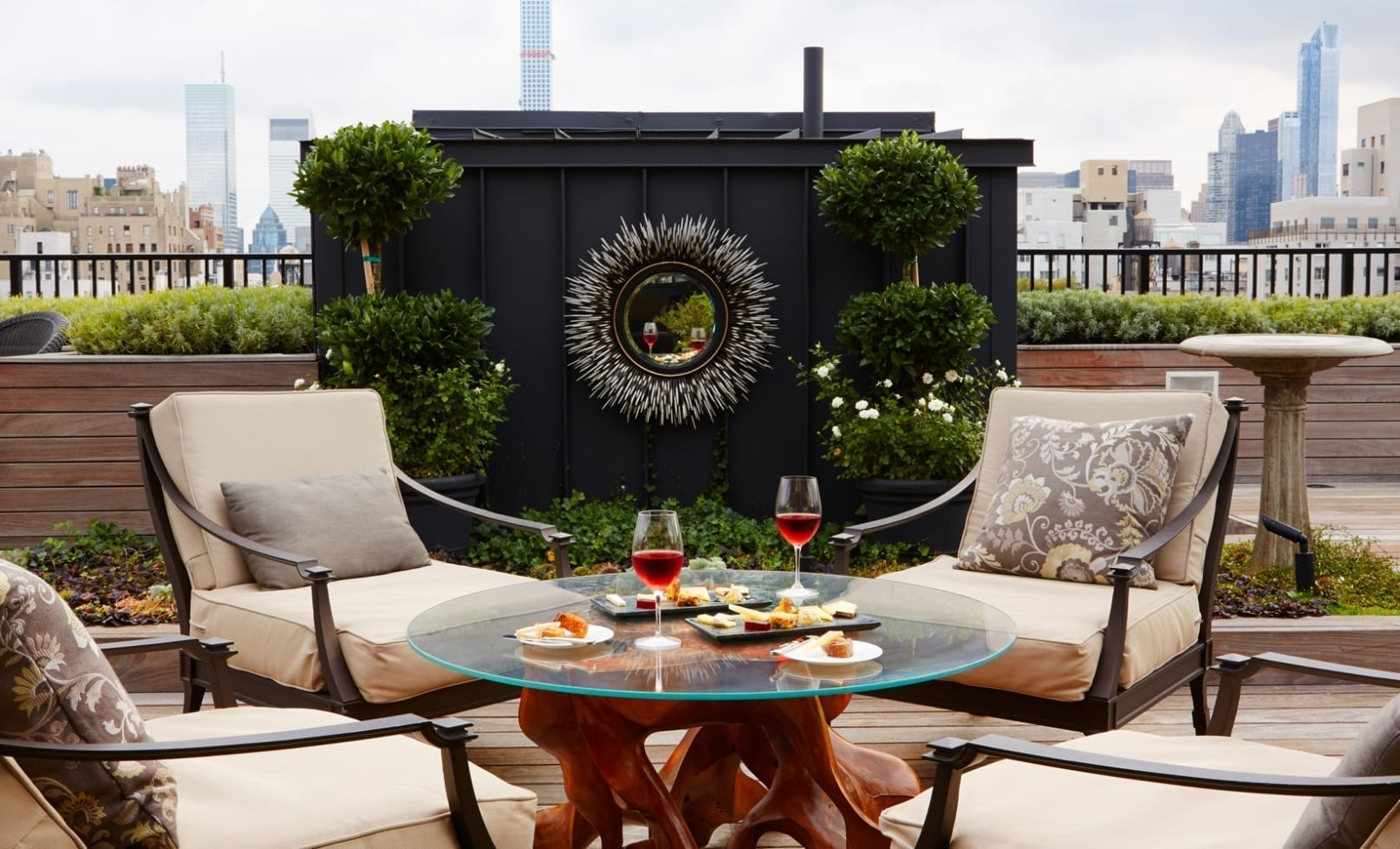 A round table set up for a wine brunch, outside on The Surrey Hotel's private roof garden. Two rectangle cheese places are placed on the glass table, with twin glasses filled with red wine.
